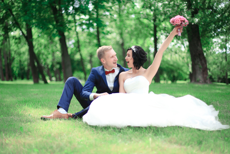 happy groom and bride sitting in the lawn Stockfoto
