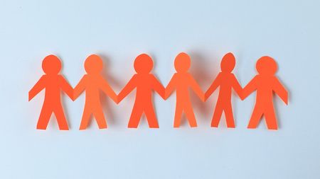 four paper men taking each others hands