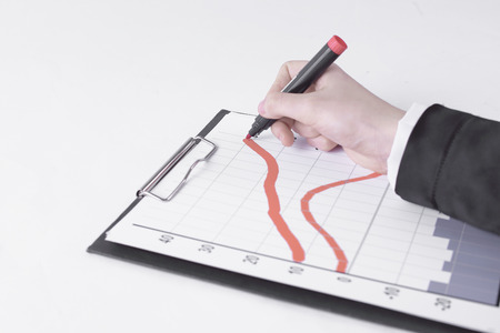 closeup .Businessman drawing a stock chart.isolated on white Foto de archivo