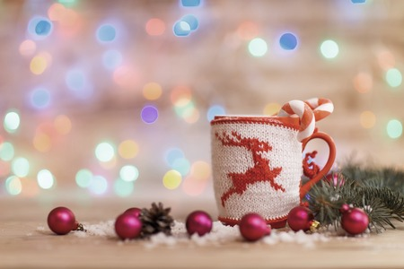 Cup for tea or coffee with Christmas knitted ornaments and Chris