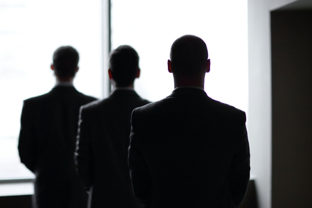rear view of three businessmen as they stare at the big window overlooking the city