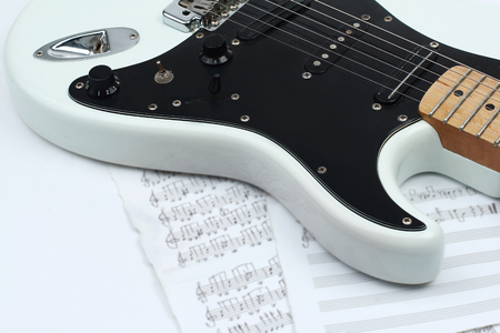closeup of music sheets and black-and-white electric guitar.iso