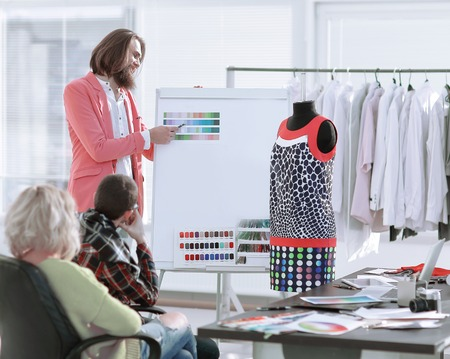 fashion designer discusses with colleagues fabric samples