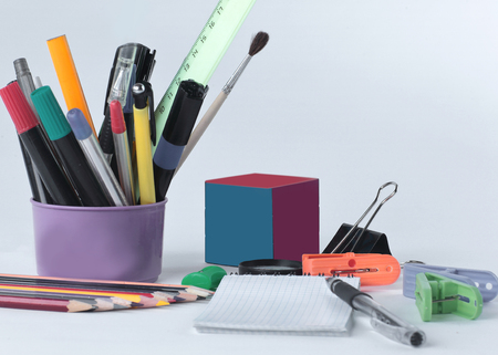Cubo di Rubik e materiale scolastico. Isolato su sfondo bianco