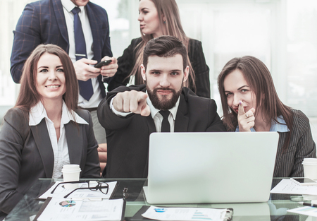 success concept in business - friendly business team showing forefinger forward