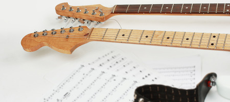 closeup .sheet music and guitar on a white background.