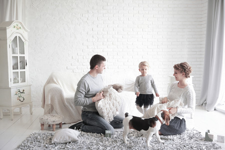 happy child with parents having pillow fight in bed at home