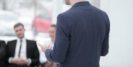 rear view.close up.businessman making a presentation at the seminar.