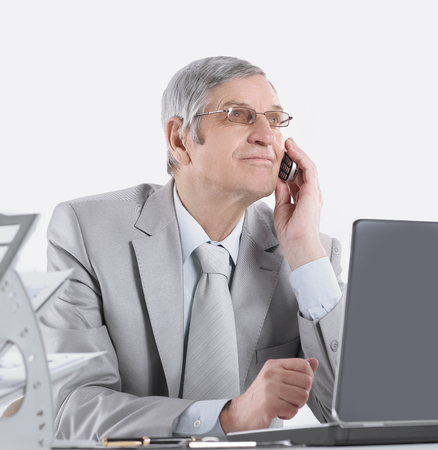 experienced businessman with mobile phone sitting at his Desk