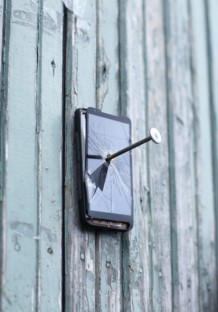 Faulty mobile phone is nailed to an old fence Stock Photo