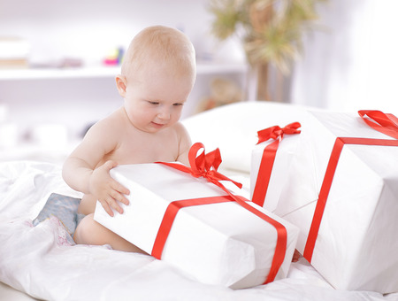pretty baby plays with gift boxes sitting on the couch Banque d'images