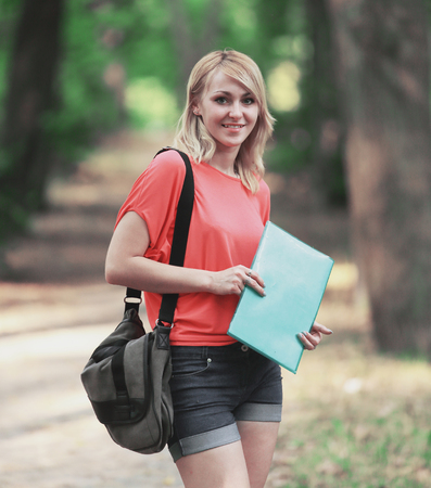 successful female student with a bag and a clipboard on the background of the Park