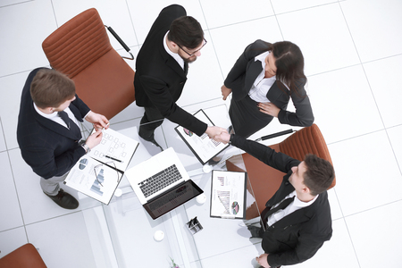 top view.handshake of business people on a work Desk
