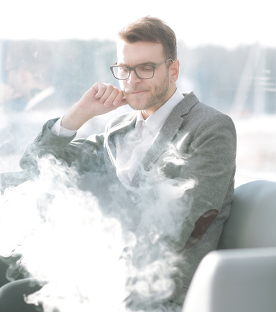 close up.pensive businessman with e-cigarette sitting in the break room