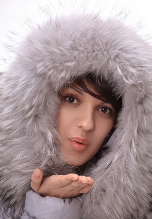 beautiful young woman in winter jacket making a kiss.
