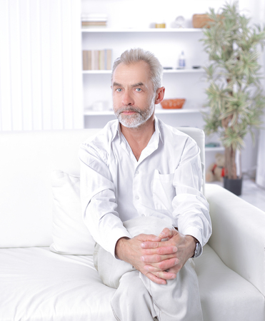 serious businessman sitting on sofa in his office
