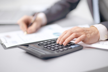 close up. the businessman uses a calculator to check the financial statement
