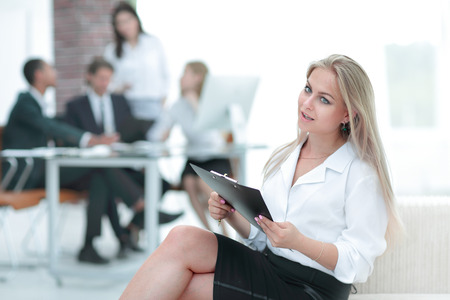 female assistant with the minutes of the meeting on the background of the office