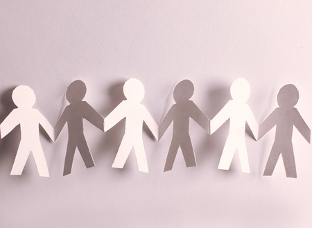 group of paper men holding each others hands
