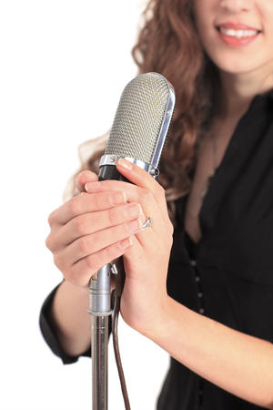 Closeup portrait of a pretty young female star performer holding old fashioned microphone