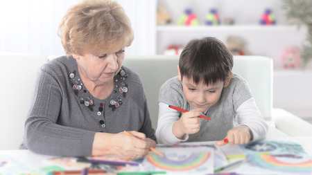 grandmother and grandson paint a rainbow in the nursery