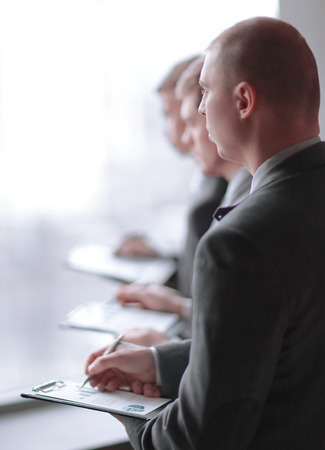 image of a businessman being at the conference and making notes on the foreground