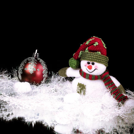 cute toy snowman on a black background
