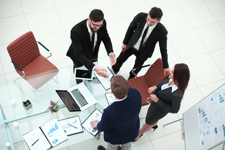 top view.handshakes of business partners on the Desk