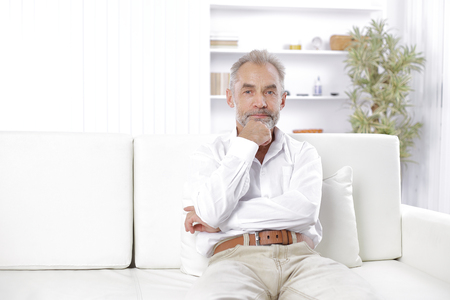 pensive Mature businessman sitting on couch in his office Stok Fotoğraf