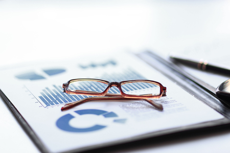 clipboard with financial report and glasses on the desktop