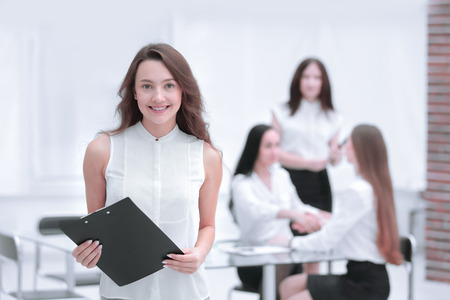 successful young business woman with clipboard in the background of the office Stok Fotoğraf