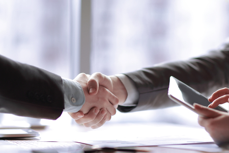 close up. the financial partners shaking hands over a Desk Stock Photo