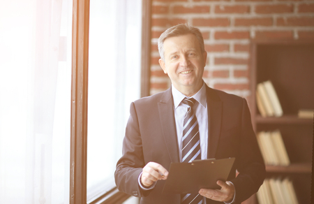 smiling senior businessman standing with document in office