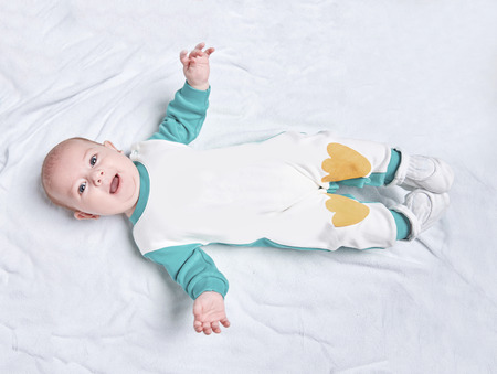 cute kid in a penguin suit lying on a blanket. Stock Photo