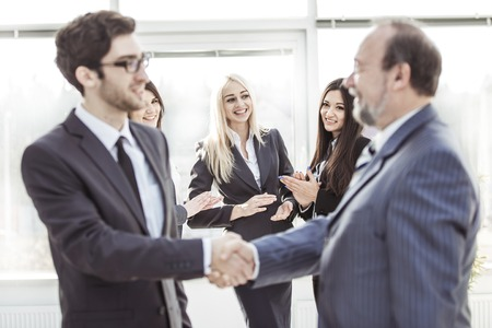 welcome and handshake of business partners on the background of applauding employees Фото со стока