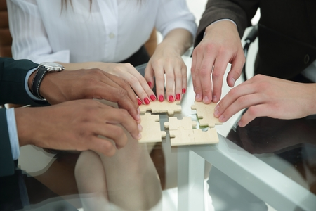 closeup .business team assembling puzzle sitting behind a Desk 写真素材