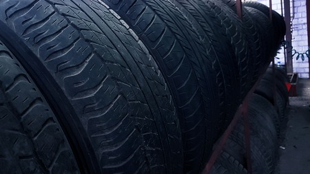 row of worn tires on a rack in the garage Stock Photo