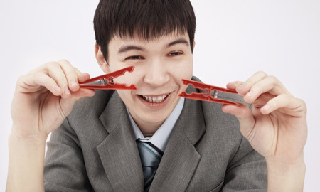 closeup.young businessman holding two clothespins,sitting behind a Desk Stok Fotoğraf