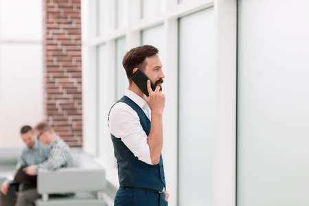 businessman talking on a smartphone while standing in the office
