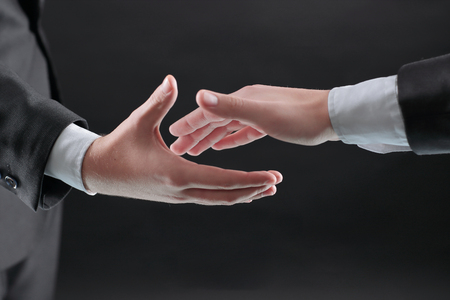 two businessmen are holding out their hands for a handshake.