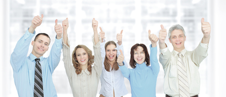 successful group of businessmen raises their hands in the office