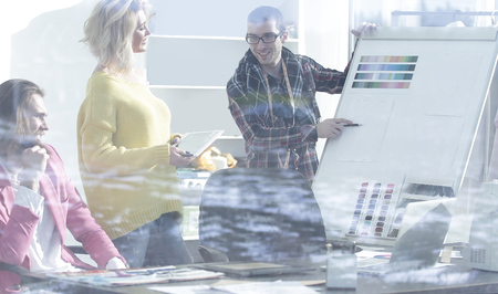 view through the glass wall. a group of fashion designers discussing new ideas
