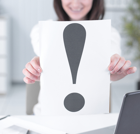 business woman showing an exclamation mark sitting at the Desk