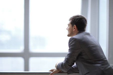 Businessman standing near the window and looking into it