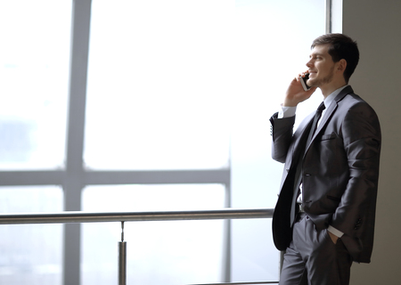 close up.businessman talking on smartphone while standing near an office window Stock Photo - 116053707