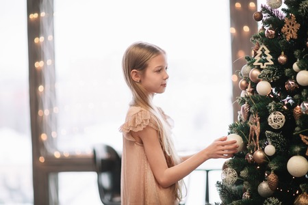 cute girl looking at the Christmas tree in her room Banque d'images