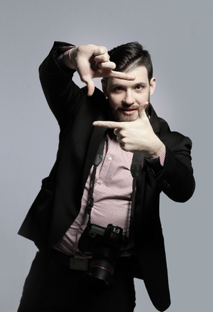 fashion photographer with a camera shows a frame from his hands.photo with copy space Stockfoto