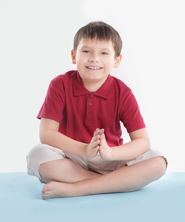 little boy is sitting in the Lotus position.isolated on white Stockfoto