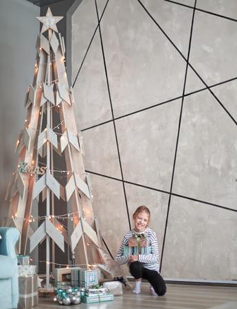 little girl sitting near a stylized Christmas tree.