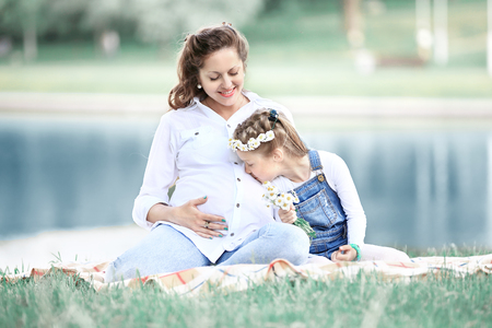 concept of maternity - pregnant mother and little daughter havin